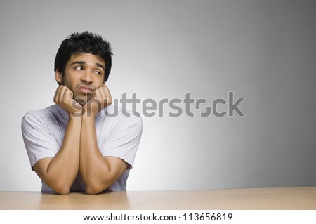 Sad man looking sideways with his hands on chin - stock photo