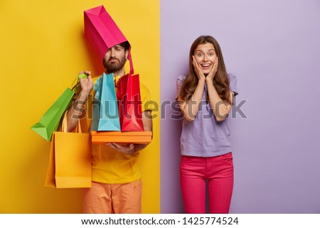 Sad man overloaded with shopping bags, has wife shopaholic, spend free time during weekend on buying new clothes, pose indoor. Positive woman rejoices successful purchases, spends money unwisely