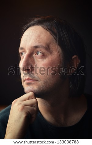 Sad man portrait, adult male looking through the window.
