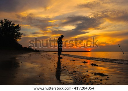 Sad man silhouette in the beach at sunset with the sun in the background. Far away concept. Alone & lonely concept.