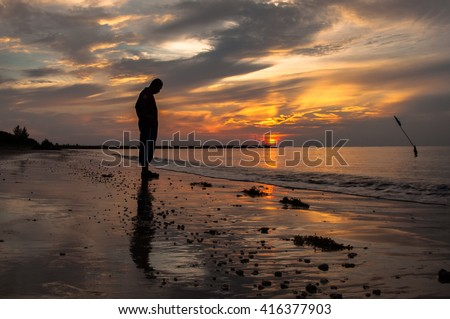 Sad man silhouette on the beach at sunset with the sun in the background