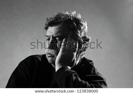 sad man sits, his head in his hand
