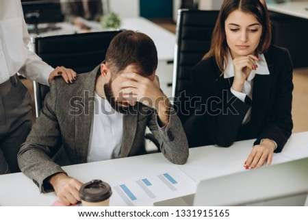 Sad man sitting at the desk in office looking at laptop screen having problem, bad news. Side view of stressed, businessman noticed the error, failed to work, failure in business concept #1331915165