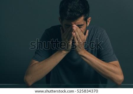 sad man sitting in dark room....