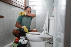 Sad man wearing gloves over his nose cleaning smelly toilets in the bathroom