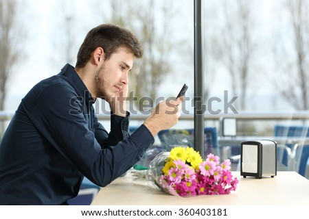 Sad man with a bouquet of flowers stood up in a date checking phone messages in a coffee shop