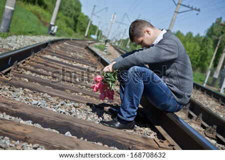Sad man with flowers sitting on the rails