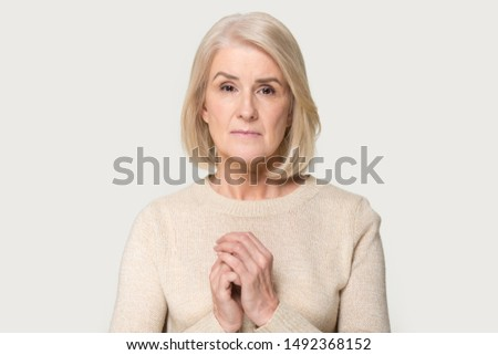 Sad mature aged woman isolated on grey studio background hold hands at chest mourning grieving, upset depressed senior female feel despair sadness, lack support or communication. Elderly help concept