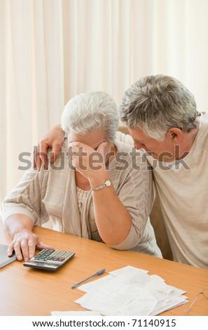 Sad mature couple calculating their domestic bills