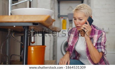 Sad mature woman calling plumber having water leaking from sink pipe. Portrait of worried aged female calling plumber crouching with basin under leaking sink pipes in bathroom