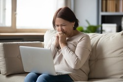 Sad mature woman looking at laptop screen and crying, sitting on couch at home, unhappy older female using computer, reading bad news, debt or bankruptcy, watching movie, making video call