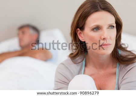 Sad mature woman on bed with her husband in the background