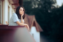 Sad Melancholic Woman Sitting in the Balcony. Unhappy lonely girl in self isolation from the world feeling nostalgic