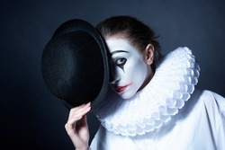 Sad mime Pierrot holding a black hat
