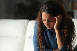 Sad mixed race woman complaining sitting on a couch in the living room at home