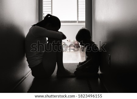 Sad mother and child sitting on the floor at home.