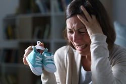 Sad mother crying missing her daughter after miscarriage holding new baby shoes at night at home