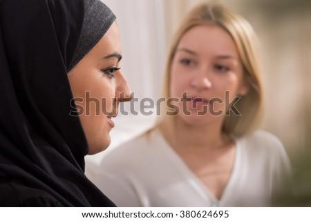 Sad muslim in hijab and young, european, blonde woman #380624695
