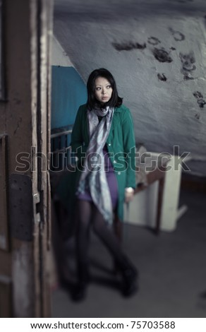 Sad old-fashioned woman indoors. Special defocus effect taken with tilt shift lens