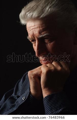 sad old man on a black background