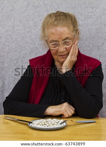 Sad old woman looking at her medicine meal