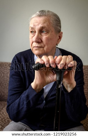 Sad old woman with a cane sitting on the couch. Old age, loneliness, health problems, memory problems. #1219023256