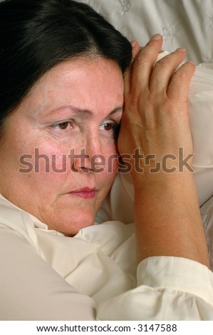 Sad older woman lying on bed, unhappy