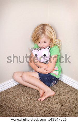 sad or lonely child in corner hugging a toy or stuffed animal