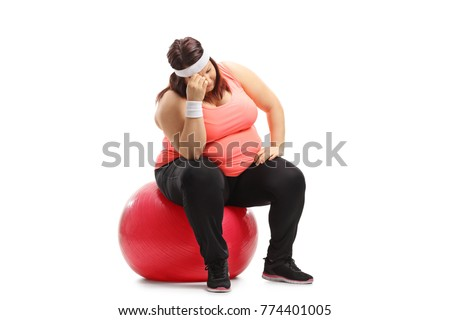 Sad overweight woman sitting on an exercise ball isolated on white background