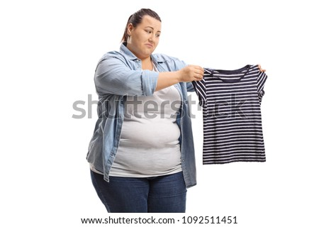 Sad overweight woman with a shrunken shirt isolated on white background