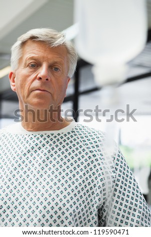 Sad patient with IV drip in hospital