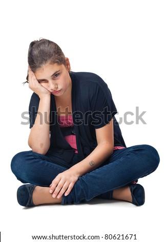 Sad, pensive girl sitting cross-legged. Studio shot against a white background. - stock photo