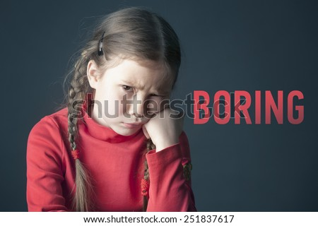 Sad pensive girl with pigtails and with the inscription Boring