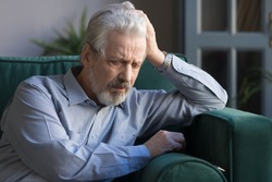 Sad pensive grey-haired mature man sit on couch lost in thoughts pondering over life difficulties, upset depressed elderly male widower think of old times, grieve for late wife, loneliness concept