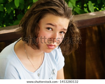 Sad pensive lonely teenager girl close-up outdoors portrait. Real people every day life