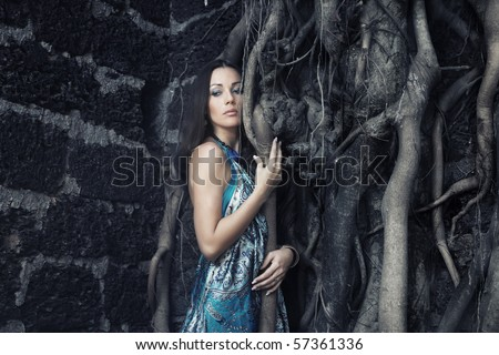Sad pensive woman at the old banyan near the ancient stony wall. Dramatic colors and darkness added