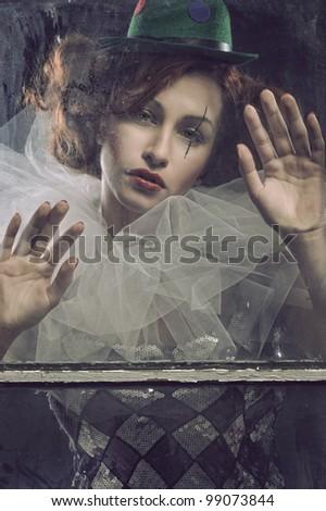 Sad Pierrot woman behind the glass - stock photo