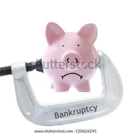 Sad piggy bank being squeezed in a Bankruptcy vice, on white