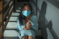 sad portrait of young scared and worried Asian Korean woman in protective mask sitting on stairs at home lockdown and quarantine during covid-19 virus pandemic in dramatic light