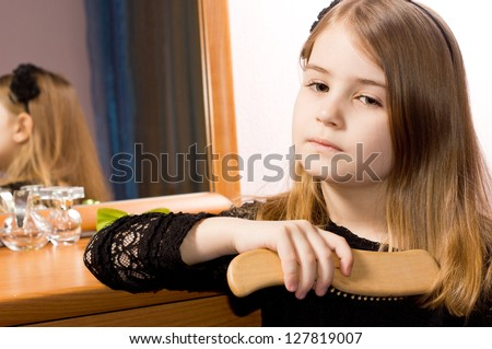 Sad pretty little girl brushing her long blonde hair with a hairbrush reflected in the mirror of the dressing table behind her