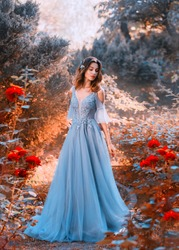 sad princess walks in fading red orange autumn garden tree withered plants, lady dark hair chic light blue dress red roses sadness, fantasy art photo young attractive girl creative colorful image