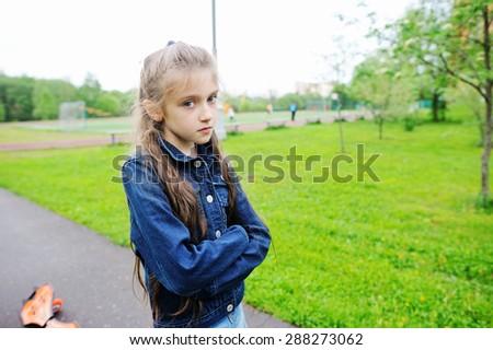 Sad school aged girl on the school yard