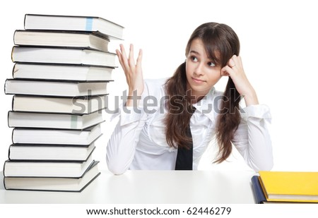 Sad school girl sitting with pile of books