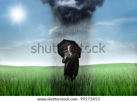 Sad senior businessman on a green meadow with downpour over him and sunny sky in the background Stockfoto ©