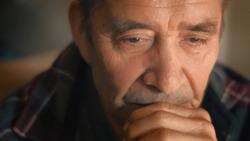 Sad senior man thinking, looking down. Closeup, shallow DOF.