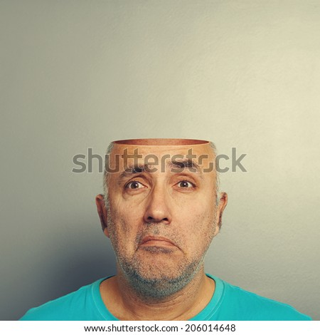 sad senior man with open head over grey background