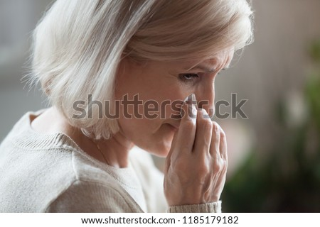 Sad senior middle aged woman widow mourning crying wiping tears, upset desperate old elderly mature lady weeping grieving lost love, having disease, suffering from depression grief divorce concept