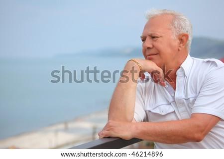 sad senior on veranda near seacoast, looking afar, lean elbows about handrail