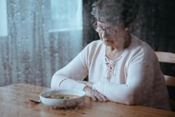Sad, senior woman having lack of appetite
