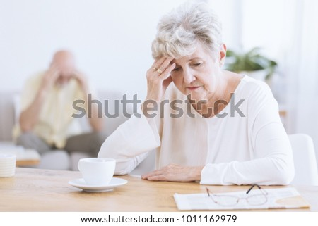 Sad senior woman sitting at a table after a quarrel with her husband Foto stock ©